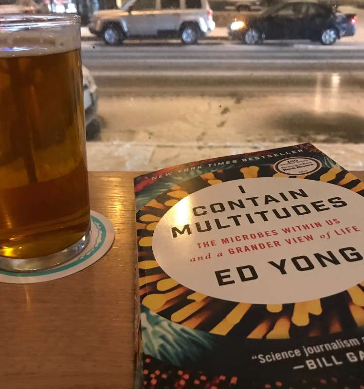 "Ed Yong's Book ""I Contain Multitudes"" on a bar with a pint of beer to the left"